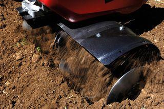 Humusfräser gräbt die Erde für eine Rasenfläche um