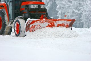 Kleiner Traktor mit Schneeschaufel befreit eine Straße von Schnee