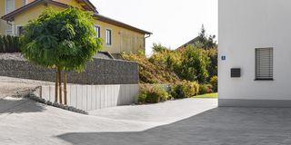Frisch verlegtes Pflaster vor einem Haus mit Natursteinen und Gabionen