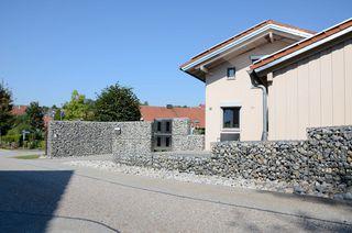 Einfamilienhaus mit Gabionen als Gartenmauer und Sichtschutz